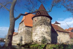 Vodní hrad Švihov se tyčí nad příkopem plným vody